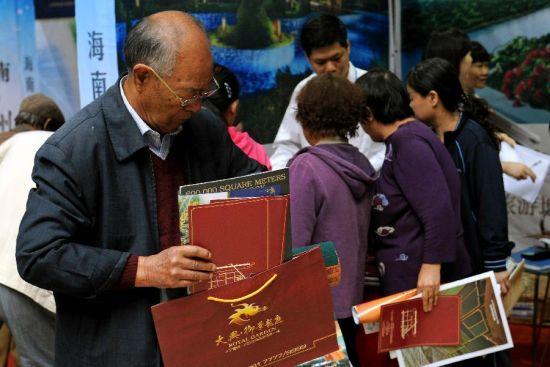 新华社照片,太原,2012年9月14日。在2012太原秋季房展会上,一名老年市民正在搜罗传单。