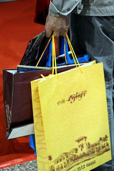 新华社照片,太原,2012年9月14日。在2012太原秋季房展会上,一名市民手里提了大量各个房产公司的传单。