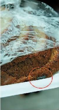 解开保鲜膜,蛋糕一角有颗耗子屎(红圈处)。
