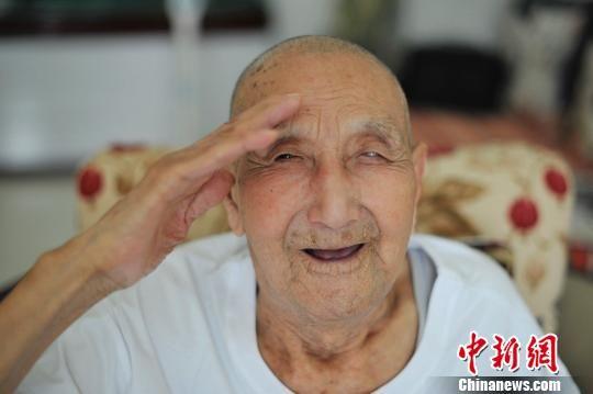2012年7月16日,关爱抗战老兵志愿者去探望老兵杨增芳,老人向志愿者行了一个军礼。韦亮摄