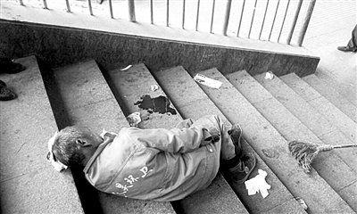 昨日,一环卫工人在清理小广告时,遭闷棍袭击,倒在过街天桥上。读者供图
