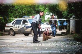 4月24日,浏阳古港镇,老镇长在清扫爆炸点附近的玻璃碎片。图/记者李坤