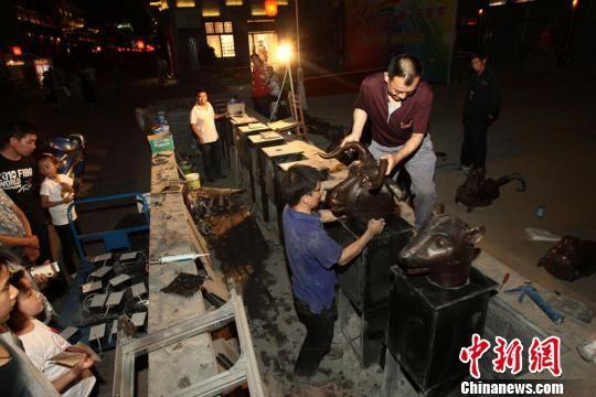 """5月31日傍晚,一组仿制""""圆明园十二兽首铜像""""在山西太原食品街做最后的搭建与调试。 张云 摄"""