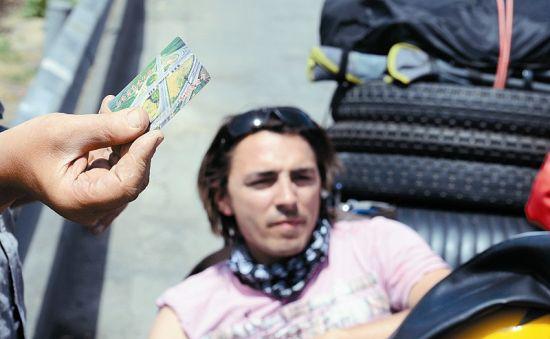 """一名 """"老外""""手里拿着的卡片上写着""""山西省高速公路车辆通行卡"""""""