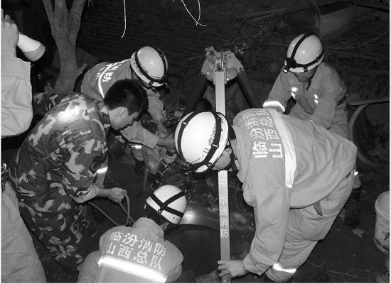 消防人员正在解救枯井中的父子二人