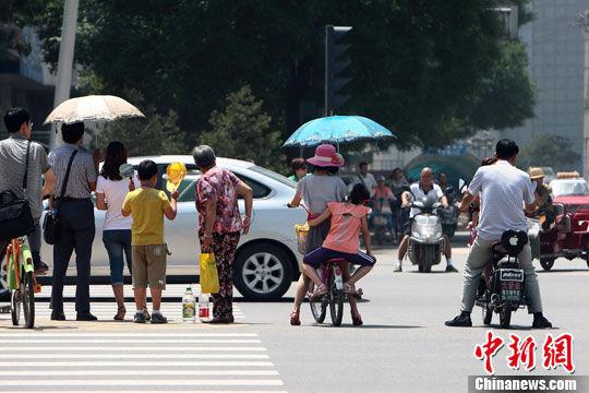 6月27日中午,山西太原气温达到34℃,市民打着遮阳伞出行。中新社发 张云 摄