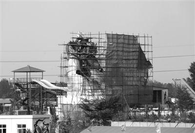 """6月29日,河南省洛阳市,工人们正在往洛阳""""大背头弥勒佛""""上安装龙头。"""