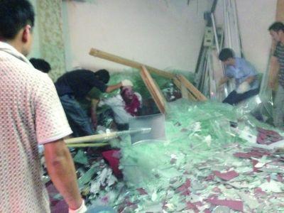 店老板被碎玻璃埋住了下半身,上身已经鲜血淋漓。