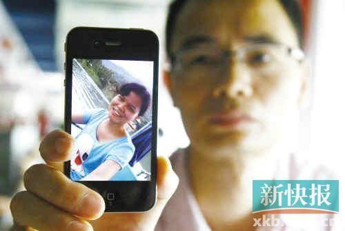 李嘉丽的哥哥拿着她的照片。记者 毕志毅/摄