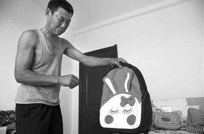 外公拿起外孙女准备下个月入小学时的新书包,不忍哭泣。新京报记者 王叔坤 摄