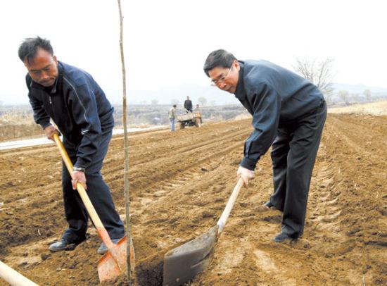 2011年4月12日,袁纯清在下乡住村联系点武乡县蟠龙镇砖壁村和村民一起种植核桃。