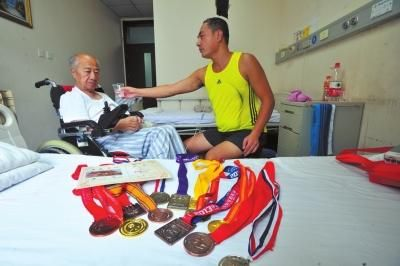 """京华时报讯(记者苗飞飞)自从2008年开始,王胜每次去外地参加马拉松长跑,都会带上年迈七旬的老父亲王元杰。截至今年7月,此前从未出过北京的老父亲,已经游历了106个城市,而开销多数来自信用卡透支。   王胜称,他今年44岁,经常会参加各地的长跑比赛,父亲王元杰和他住在一起,此前从没有离开过北京,每天在家中也没什么业余活动。""""当初住在平房,邻居们联系得紧密些,自从搬上高楼之后,邻居间的联系也少了,平时基本没有交流。""""   王胜说,他担心父亲难耐寂寞,2008年他去上海参加马拉松前,产生了带上父亲随行的想法,那年父亲71岁。   王元杰老人表示,起初听到这个想法时非常犹豫,""""我都已经70多岁了,万一路上生病不是给孩子添麻烦吗?""""王胜费尽心思终于劝服了父亲随行。   """"那次是我爸爸第一次在外面宾馆睡觉,晚上早早地上了床,但是一直到深夜都没有睡着觉。他很兴奋,但又怕被我看出来。""""王胜说,当时看到父亲的样子真是心酸,""""这么大年纪的人了都还没有出过北京城呢""""。   自从参加完上海马拉松后,王胜每次出去参加比赛都会带上父亲。王元杰老爷子在几次出行之后也对自己的身体有了信心,愿意跟随儿子出行。   王胜说:""""比赛的时候我父亲就去现场给儿子加油,有的时候他在宾馆看电视直播。比赛结束了我们就吃点当地的小吃,在当地玩玩。""""   5年来,王胜已经带着父亲走过了上海、浙江、青海、福建等17个省份的105个城市,还曾经随团去了一次朝鲜新义州。   每次父子两人都是选择火车出行,""""动车、高铁,更多的时候都是普通的火车"""",王胜说,除了安全上的考虑,还有经济上的因素。至今为止,王胜家中的房贷尚未还清,5年间带父亲出行总共花费6万余元,多数来自信用卡透支。王胜的哥哥对此表示理解,并适当给予了一些经济上的帮助。   通过5年的旅游,老爷子已经学会了使用数码相机,学会了在网上查询旅游攻略。王胜说父亲""""赶上了潮流""""。   今年7月,王元杰老爷子在家中突发脑血管疾病,被送往航空总医院接受治疗,目前已经进入康复阶段。""""康复之后还要跟着儿子出去跑"""",王元杰说。"""