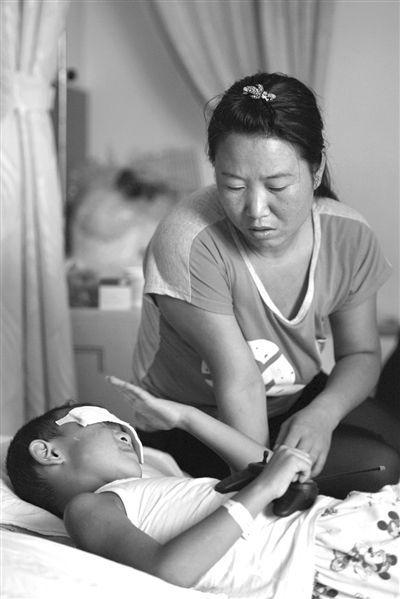 9月4日,山西省太原市眼科医院,小斌手握玩具。当日,小斌听到警方破案的消息立即躲在母亲的怀里。图/CFP