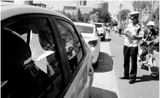 交警正在对辖区内违规停放的机动车,开具处罚通知单。