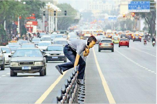 省城府西街国贸大厦门前,一位市民边打手机边翻护栏。 晨报记者 郝晨光 摄