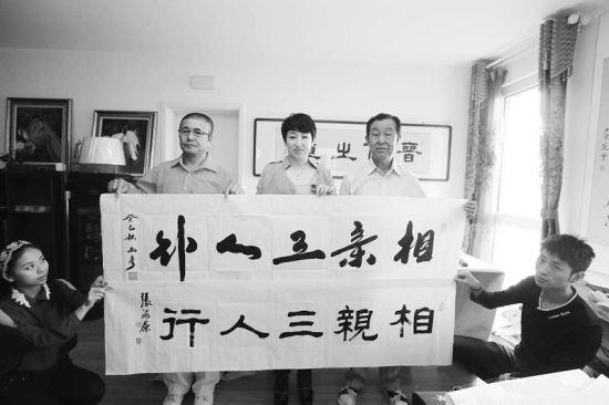 薛淑琴(中)接收张海原(右)、马丙彦为影片题写的片名字画。