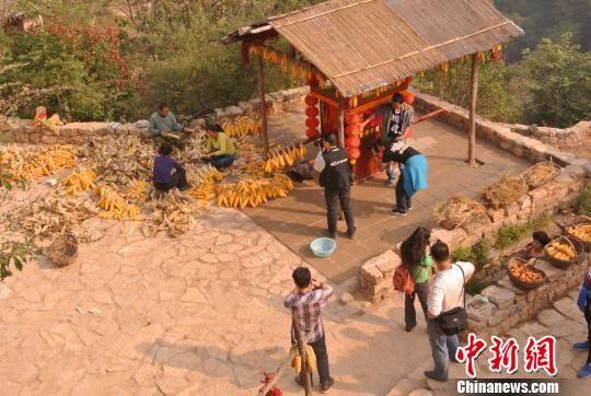 在塔尔坡古村落内,当地村民正在收获、打理玉米。 李新锁摄