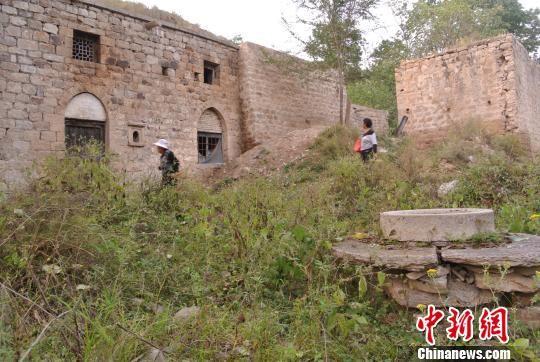 山西乡宁县安汾古村内,当地村民从唐代县城遗址前走过。 李新锁 摄