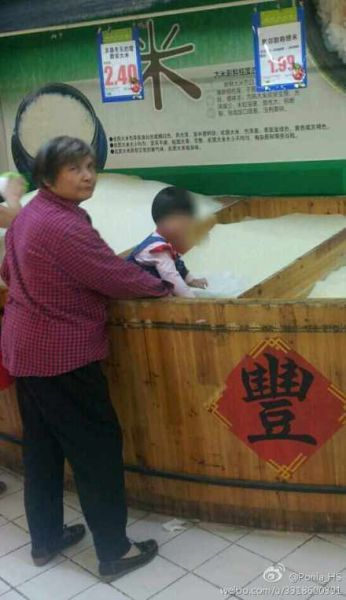 老太将小孩子放入米桶中玩耍。