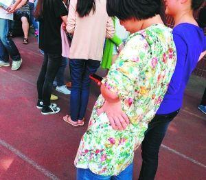 图为在重庆铁路中学校园,经常看到学生在玩手机。