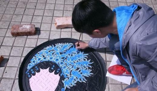 的周崇崇正在给花旦的头饰上色.  涂鸦窨井盖照片引发关注.一个个图片