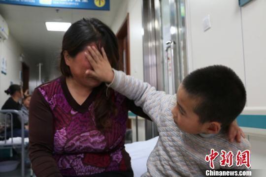 看到妈妈难过哭泣,小斌杰懂事地给妈妈擦泪。 李超庆 摄