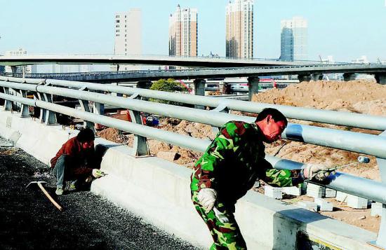 南中环街与太榆路的立交桥上,施工人员正在粉刷护栏。牛晨阳 摄