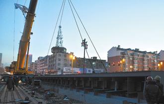 图为重型吊车正在吊装钢结构桥身。