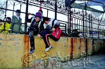 爬墙通过的小学生有时两人一同挤进来,看起来不安全