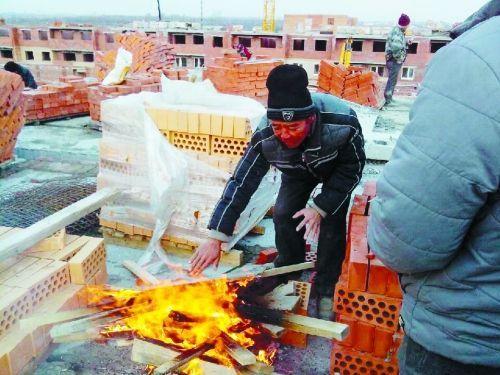 在俄罗斯工地打工时,因为天太冷,工人不得不在工地生火取暖。