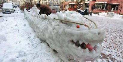 长龙雪雕制作用了3天,眼睛是用橘子做的 本组图片 本报记者 王强 摄