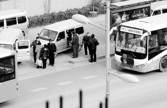 """""""黑车""""司机在公交站牌下肆意揽客。晨报记者 马俊明 摄"""