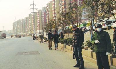 公交站牌在绿化带里,市民只好站在快车道上等公交。
