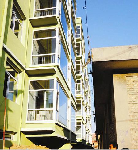 运城新亚达房地产开发有限公司盖成的楼房离民房不到一米远。