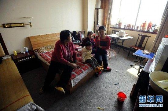 """四世同堂的王爱连(左一)一家在太原迎西大厦的""""新家""""里看电视(2013年10月28日摄)"""