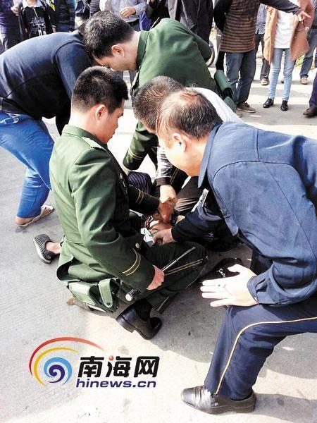 两名边防民警将持刀男子按倒在地,旁边的群众也过来帮忙。(图由市民陈先生提供)