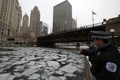 资料图:2013年12月19日,美国芝加哥一名警察对着河上的浮冰拍照。