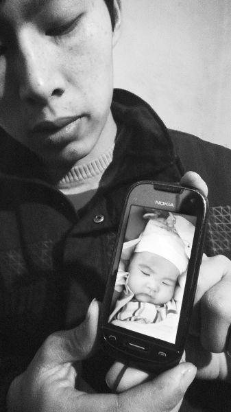 小柯翻出手机中孩子生前的照片。 记者 戴维 摄