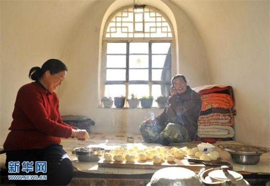 """1月17日,山西省阳曲县杨兴村,父亲庞志同(右)和母亲王绿仙在家里蒸包子。他们想对在天津读书的儿子庞文陶说,""""陶陶,赶快回家吧,妈妈给你蒸了大包子,是你最爱吃的豆沙馅儿。"""" 小年到了,除夕近了,慈母盼着游子回家又是一年。 新华社记者燕雁摄"""