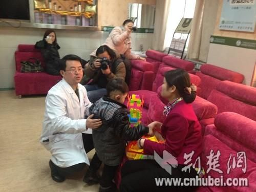 图为:医生在向记者介绍失耳儿童小凡凡的病情