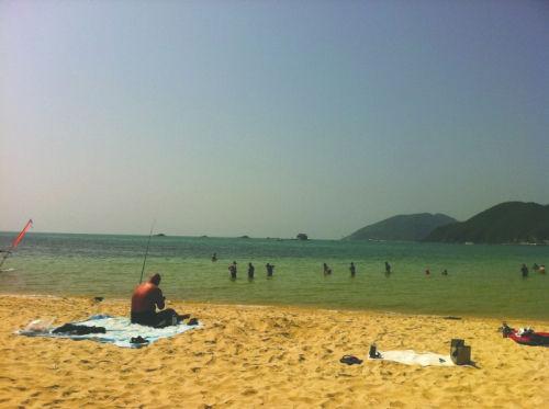 17日,一名银屑病患者在大东海沙滩晒太阳