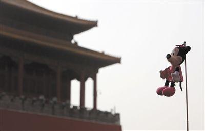 """北京旅游团队中,一名导游在自己的旗杆上绑了一只""""米老鼠"""",好奇地张望。资料图片/新京报记者 吴江 摄"""
