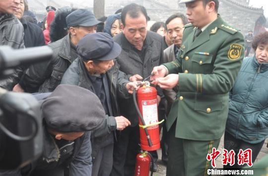 平遥县为平遥古城居民免费配发灭火器。图为消防人员教居民如何正确使用灭火器。 王青芳 摄