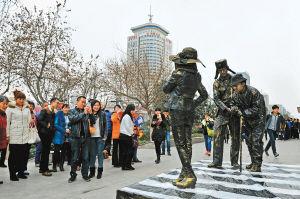 市民在弘扬尊老爱幼精神的活雕塑作品《大爷您慢点》前观赏、拍照 记者 李念 摄