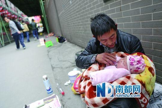 3月5日,广州大佛寺门外,父亲带着两个月大的女儿乞讨。南都记者 张志韬 摄