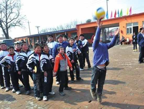 2012年3月20日,孩子们兴高采烈地玩着志愿者送来的新排球。
