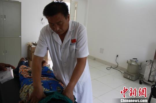 图为王维忠正在为患者治疗。