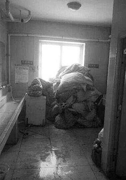 昨日,沈阳体育学院武术学院男生因没叠被受到惩罚,他们的被子被扔进了宿舍厕所。 网友供图