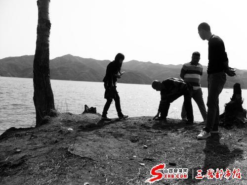郭补全(左二)在水库警示碑位置向记者介绍事故发生情况。
