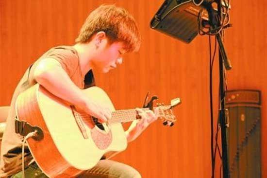 王景皞在演奏吉他。